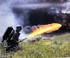 A German solider aims a backpack flamethrower across a field of tall grass Soviet Union 1941 or 1942 The image was originally published as 'Das Heer...
