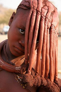 Yves Picq . Namibie Himba.   The Himba women wear their hair in long braids and cover them with a mixture of butter fat and ochre called otijize which also gives their skin a red tint. Its a common trend and symbol of beauty.