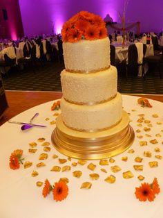 Gold/cream/orange round stacked 3 tier wedding cake with orange sunflowers