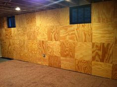 """We had Lowe's cut 2'x2' squares of plywood.  We used 1""""x2""""s and a tap-con to attach to the cement block walls. We also added foam board insulation and then used a nail gun to hang the squares with contrasting grains on the walls in our basement. A nice man-cave."""