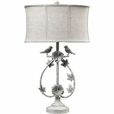 "Cast a stylish glow in your master suite or favorite reading nook with this eye-catching iron table lamp, featuring a garden-chic design and distressed white finish.     Product: Table lamp   Construction Material: Iron and linen     Color: Distressed white   Features:   3-Way switch   Naturally-inspired bird and branch design           Accommodates: (1) 100 Watt medium base bulb - not included Dimensions: 31"" H x 18"" Diameter"