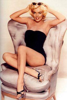 Marilyn Monroe in a black bathing suit and lucite heels.