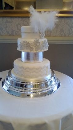 Beautiful Art Deco wedding cake.  White and Silver colour scheme, using edible silver leaf. Diamante and feather head piece finishes the design .