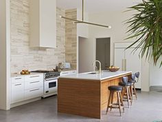 Designer Angie Hranowsky completely transformed the  Charleston, SC, home of author and screenwriter Carolyn Evans and her husband, Ray, with a few smart changes to the layout. In its new spot, the spacious, light-filled kitchen boasts a countertop-to-ceiling travertine backsplash by Anne Sacks. Look closely and you'll see a shiny brass reveal between the Custom Creations walnut island and its Caeserstone top. Suspended above the island is an Apparatus fixture.