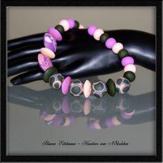 Diese Kette besteht aus 30 handgefertigten Perlen, aufgereiht auf Schmuckdraht, verlängert mit einem feinen silberfarbenen Gliederkettchen.     Die Pe