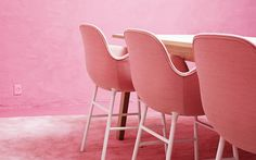 Soft pink upholstered Form armchairs in a pink tone-on-tone interior