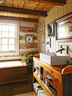 Log-Cabin Chic  This cabin bathroom mixes stone with natural and painted wood to create a cozy escape. A big window over the soaking tub brightens what could otherwise be a very dark room.
