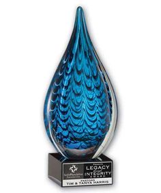 This fascinating sculpture is called the Glass Mythic Award. It is a hand blown art glass featuring rich blue hues suspended in clear glass. Clearly stunning, this recognition award is elevated on a black base featuring a black steel plate with laser engraved copy. Packaged in individual boxes. If you have any questions, or if you would like to place an order please call us now at 800-377-8646.