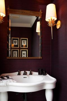 Purple powder room boasts walls clad in purple grasscloth lined with a black and gold French mirror over a Parisian pedestal sink fitted with bronze fixtures lit by gold wall sconces, Worlds Away Delilah Gold Leaf Sconce.