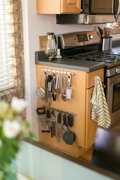 attach hooks to hang your utensils on the side of your cabinet.