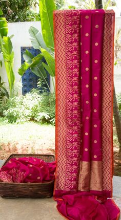 This magenta sari is a Benares silk with gold zari bhuttas all over. The border and pallu have a beautiful design in gold zari adding a traditional charm to this sari