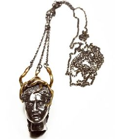 The Medusa Necklace handmade by Aesa - there's a hand holding the serpent chains of Medusa's hair.