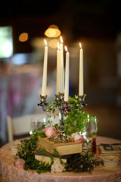 Mixed matched candelabra centerpieces stacked on  vintage books with draped green vine & blooms     Rustic Barn Wedding Skinner Barn Vermont  http://storyboardwedding.com/jessica-poole-wedding-anniversary-skinner-barn-vermont/