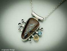 Rhapsody Australian Boulder Opal Sterling Silver Necklace  A brown-toned Australian Boulder Opal with faint accents of blue and yellow. Those colors are accented with yellow Citrine and Swiss Blue topaz faceted gemstones. The pendant is attached to a 17-inch sterling silver chain, plus a 2-inch extender.  The back has been stamped with the .925 hallmark and makers mark. The stone part of the pendant measures 1-inch (27mm) high by 1/2-inch (15mm) wide at the widest. Item: NS-206  =&#...