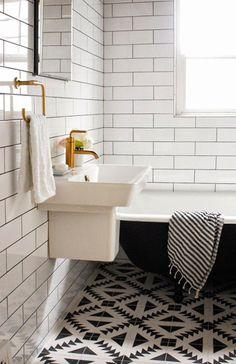 salle de bain retro avec carrelage noir et blanc et baignoire sur pieds