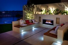 This outdoor room with modern #fireplace would be better without the weird lighting in the bushes.