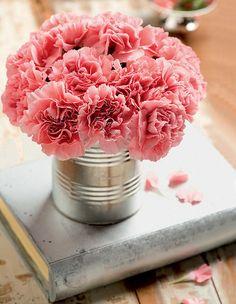Um vasinho simples, feito com uma lata de molho, pode ser colocado no criado-mudo dela. O buquê de cravos rosa completa o mimo cheio de amor