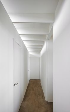 walls of hallway/stair wall? doesn't reach ceiling. joists/lighting show through, create awareness of more space