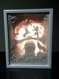 NEW PRICE- was $250, on sale for $149. Custom art piece, locally designed and hand assembled. Makes a lovely decorative piece or can be a unique one-of-a-kind gift for Game of Thrones aficionados. Inspired by Game of Thrones, this lighted shadow box has a white wood-frame with overall dimensions (LxWxH): 15in x 12in x 2.75in. Construction is of paper-cut card-stock assembled in layers providing a 3D perspective into the battle for the Iron Throne between the dominant families of Westeros....