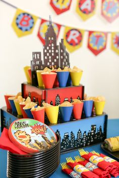 This foam table decoration and snack station, aka #Superhero City Tray, includes paper cones to hold popcorn, candy, chips, or other snacks. Or, you can use the tray as a cupcake stand. Available as part of the Comic Book #EviteParty in a Box for 16 guests.