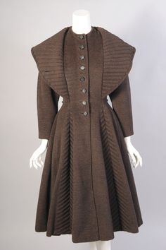 A subtle black and brown striped wool is used for this charming Lilli Ann coat. The collar can be worn in two ways for added drama. It is trapunto quilted to match the V-shaped quilted panels on either side of the skirt. The fitted bodice has 1950s Style, Vintage Outfits, Vintage Dresses, 1940s Fashion, Vintage Fashion, New Look Coats, Vestidos Pin Up, Mode Mantel, Vintage Mode