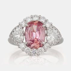 An untreated padparascha (orangy pink sapphire) and diamond ring. Untreated padparascha , 3.043cts, according to certificate from SSEF. Brilliant-cut and heart-shaped diamonds, total carat weight circa 1.75cts. Size 17/53. 18K white gold.  Estimation : 26.229€/28.415€