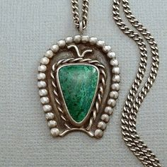 A Gorgeous Old Pawn Vintage Native American Navajo Necklace Pendant, Handmade in Solid Sterling Silver with 22 Vintage Curb Link Sterling Silver Hallmarked Chain featuring a Bezel-set Exquisite Green Chrysocolla Gemstone framed with Twisted Rope in a Naja Shape Sterling Tested Setting, Weight 15 Grams circa 1930 to 40s!  Measurements for the Pendant are 1-1/2 in length by 1 in width. The Chain measures 22 in length.  This Navajo Pendant has the Fine Character of the Old Wild West! It is Old…