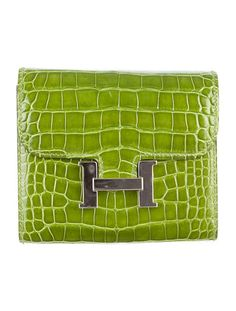 Pelouse Hermès crocodile constance compact wallet with silver-tone hardware, interior zip pocket, four card slits, front magnetic closure and back pocket. Stamped Square M 2009.