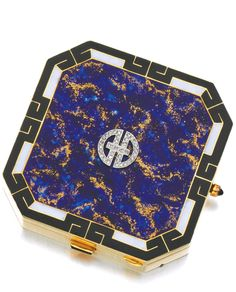ENAMEL AND DIAMOND POWDER COMPACT, 1920S The octagonal shaped powder compact decorated with blue and gold enamel, framed by a geometric border of black and white enamel, set to the centre with a circular rose diamond motif, containing a powder compact and mirror, measuring approximately 48 by 48 by 10mm, signed Walser-Wald, French assay and maker's marks, suede pouch.