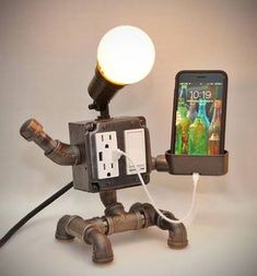 Robot Steampunk Industrial Pipe Desk Lamp with Dimmer, 2 AC & 2 USB outlets, Smartphone Charging Cradle, optional Apple Watch Charger AirBnB - This lamp is a cute yet very functional addition to any room. Perfect for your night stand, this la -