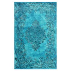 Anchor your living room or define areas in the den with this hand-tufted wool and art silk rug, showcasing a scrolling botanical diamond motif in blue.