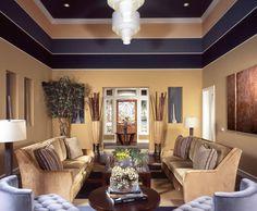 Ein warmes Beige auf dem unteren Abschnitt der Wände ist durch dunklere Streifen Purpur akzentuiert, die Farbe aus den blass Lavendel-Stühlen auf der einen Seite des Raumes zu ziehen. In Zimmer mit hohen Decken kann das Hinzufügen von Behandlungen auf den oberen Teil der Mauer ein Zimmer mehr gemütlich fühlen machen.