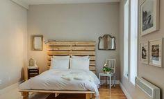 tête de lit palette de bois brut, peinture murale gris taupe, literie blanc neige et sol en parquet contrecollé