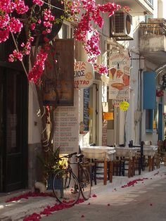 Sidewalk cafe in #Koroni, Greece, a quaint town nestled on a hill below an impressive Venetian castle and reaches to the edge of the gulf. I love these little sidewalk cafes where one can sit and watch daily life in a town far from home.  ASPEN CREEK TRAVEL - karen@aspencreektravel.com  (photo via aegitna)