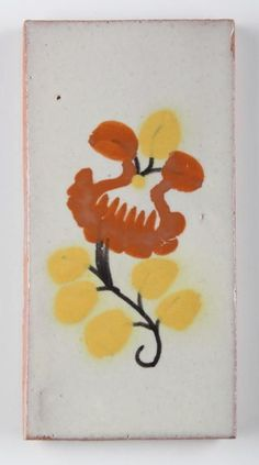 A glazed terracotta tile with brown and yellow flower design purchased in Mexico to be used in the bathroom of Marilyn's home.