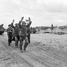 JUN 6 1944 0800: Green Howards land on Gold Beach German POWs being escorted along one of the Gold area beaches, 6 June 1944.