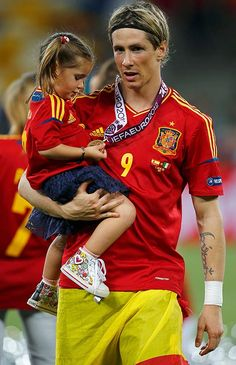Fernando Torres holds his daughter Nora as he celebrates after defeating Italy to win the Euro 2012 final soccer match at the Olympic stadium in Kiev, July 1, 2012.