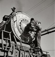 "March 1943. ""Needles, Calif. Electrician B. Fitzgerald cleaning the headlight of a locomotive at the Atchison, Topeka & Santa Fe yard. All engines operating west of Needles are equipped with hooded headlights in accordance with the blackout regulations."""