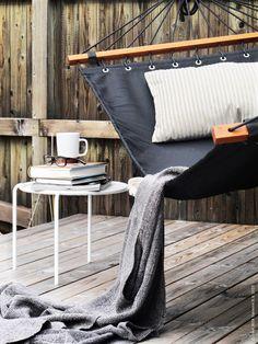 En trave bra böcker, en kopp te och tidningen är vad som behövs för en lugn stund i FREDÖN hängmatta, LUKTNYPON kuddfodral, GURLI pläd.