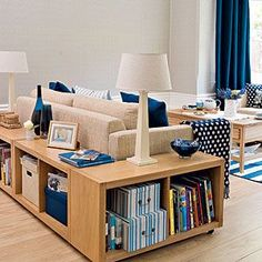Living room storage in a wrap around sofa back unit. Imagine the space it saves, while providing attractive storage. I'm thinking that this idea would look equally chic built from recycled wood, filled with rustic baskets, fabric covered boxes and my Books Worth Re-Reading collection. Now, candelabras in place of lamps, and ceramic where now you see glass. Ahh!!! Perfect