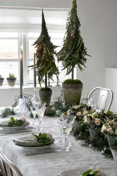 Juleboddækning med masser af blomster, eukalyptus, gran og kogler på både dug og servietter tilsat glaskugler og en masse levende lys. // For e true Nordic Christmas table setting use white and and decorative elements from nature such as spruce, pinecones and eucalyptus. #feminadk #christmas #tablesettings #jul #juleborddækning