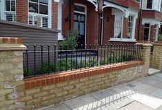 yellow stock brick wall and metal rail with hedge and bike storage