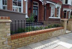 yellow stock brick wall and metal rail with hedge and bike storage