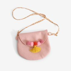A sweet little purse in a soft pink wool/rayon felt. Lined inside with orange mini gingham, with orange and white floral cotton strap. Pretty yarn pompoms and vivid yellow tassle line the edge of the
