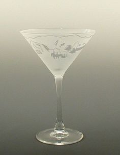 Scenes from a perfect little wintertime mountain town are etched onto these martini glasses. Hand decorated in USA.