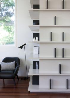 minimalistyczna zabudowa w kształcie litery L. Nietypowy regał na książki i bibeloty, który dobrze wygląda nawet jak jest pusty.
