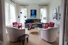 Modern living room with gray slipcover sofa with teal blue velvet pillows, Queen Elizabeth pop art, modern chairs upholstered in David Hicks...