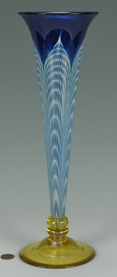 """rt glass trumpet shaped vase with peacock feather design in blue and white with round yellow foot. Unsigned, attributed to Durand (Vineland Flint Glass Works), 1924-1931. Measures 13-1/8"""" H. Condition: Some light scratching on base, with one 1/8"""" scratch being somewhat deep."""
