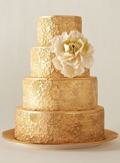 Embossed with an intricate pattern, this tiered gold wedding cake is embellished with a single, dramatic flower.
