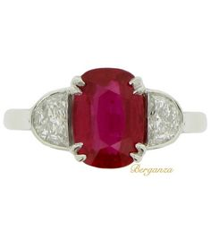 An Art Deco platinum, natural Burmese ruby and diamond ring, English, circa 1935.  Set with a natural unenhanced oval old cut Burmese ruby in an open back double claw setting with an approximate weight of 2.08 carats, flanked by two D-shape old cut diamonds in open back rubover settings to an openwork linear gallery with intricate pierced scallop patterning and backholing, flanked by elegant inward tapered gently sloping shoulders with cheniers to a solid D-shape shank.